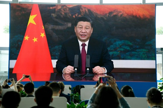 A video screen shows Xi Jinping giving an online speech at the Boao Forum for Asia
