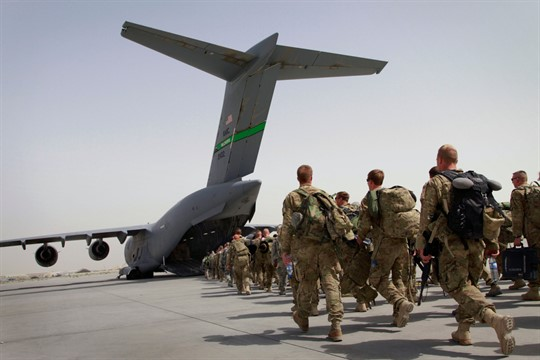 U.S. soldiers walk toward an American military plane as they leave Afghanistan