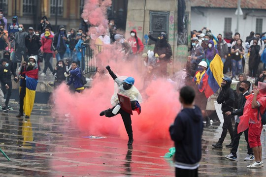 An anti-government protester returns a tear gas canister at the police during clashes in Bogota