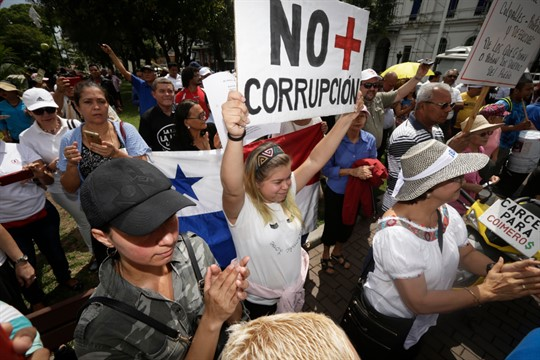 """A protester holds up a sign that reads in Spanish, """"No more corruption,"""" in Panama City"""