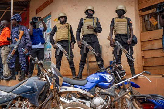Soldiers stand outside a polling station in Kampala, Uganda