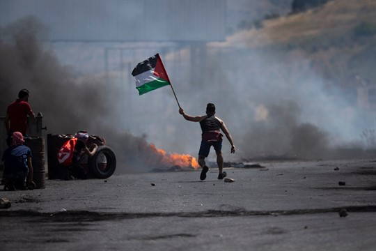 A protester waves the Palestinian flag during clashes with the Israeli forces at the Hawara checkpoint