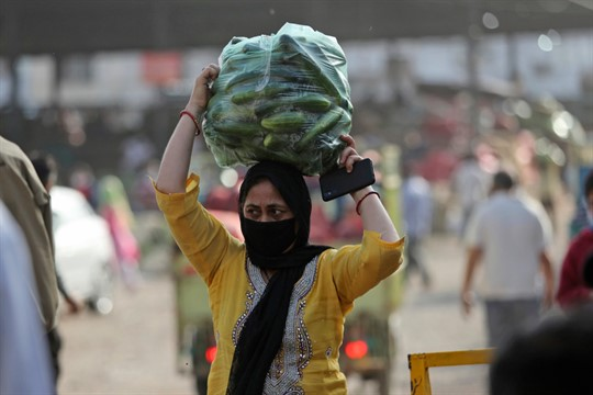 A woman carries vegetables outside a wholesale market in Jammu, India