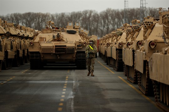 A U.S. soldier walks past parked armored vehicles and tanks in Antwerp, Belgium