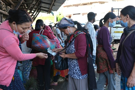 A woman hands money to a vegetable vendor at a market in Kohima, India