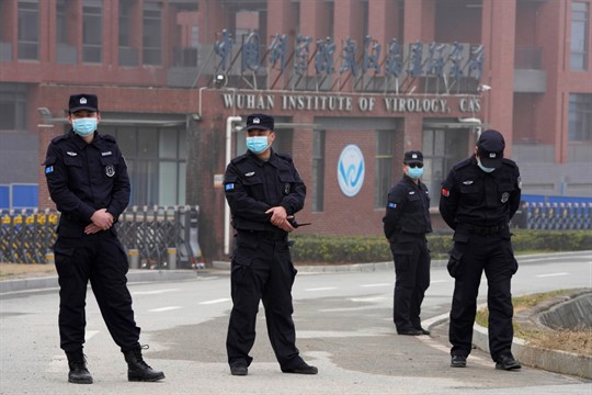 Security personnel gather near the entrance of the Wuhan Institute of Virology