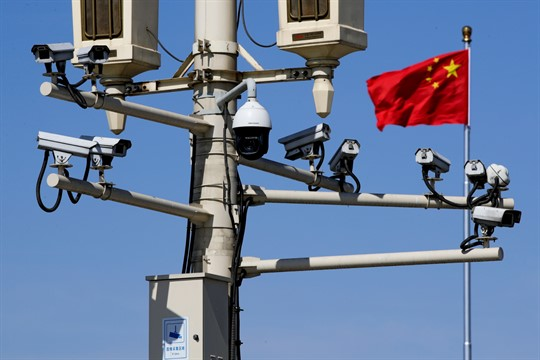 A Chinese national flag near the surveillance cameras in Tiananmen Square, Beijing