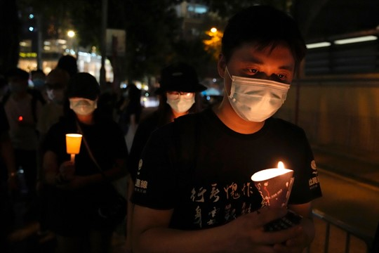 People walk with candles to mark the anniversary of the Tiananmen Square massacre, in Hong Kong