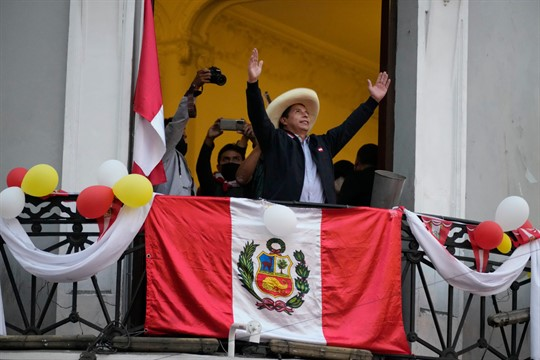 Presidential candidate Pedro Castillo greets supporters at his campaign headquarters the day after a runoff election