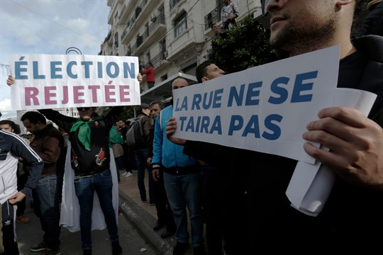 """Algerian demonstrators protest the 2019 presidential election with banners in French that read """"Reject the elections"""""""