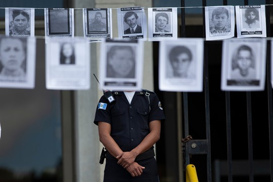A police officer standing outside Guatemala's Supreme Court, between photos of persons who were forcibly disappeared