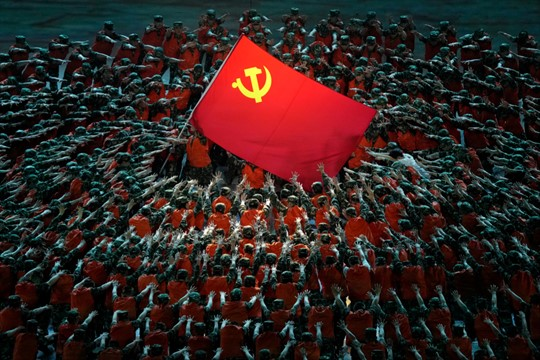 Performers dressed as rescue workers gather around the Communist Party flag during a gala show