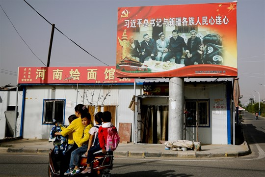 A banner showing Chinese leader Xi Jinping with a group of Uyghur elders, Xinjiang