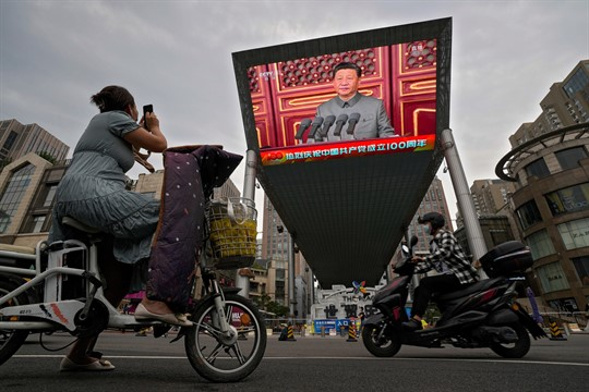 A large video screen showing Xi Jinping delivering a speech to commemorate the CCP's 100th anniversary