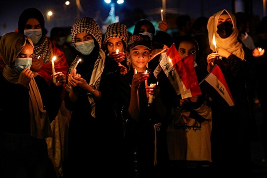 Demonstrators light candles to mark the first anniversary of the anti-government protests in Basra, Iraq