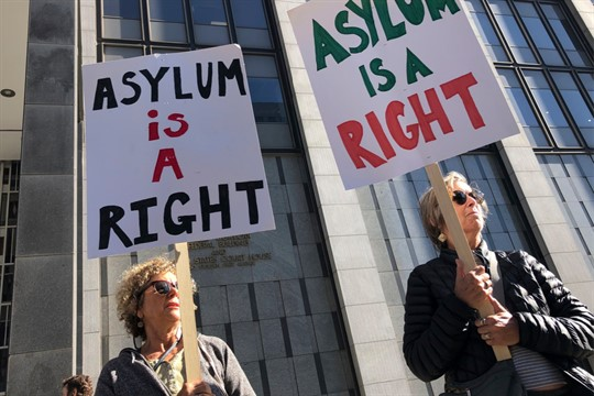 """Protesters hold signs that read """"Asylum is a Right"""" outside of the San Francisco Federal Courthouse"""