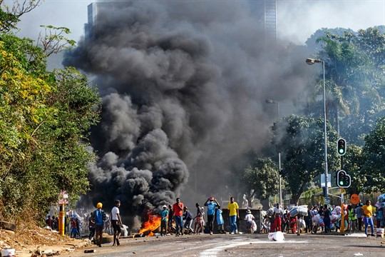 Looters outside a shopping center alongside a burning barricade in Durban, South Africa