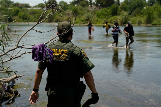 A Border Patrol agent watches as a group of migrants walk across the Rio Grande