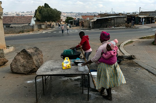 Women pack up their roadside food stall in Alexandra Township, north of Johannesburg, South Africa.