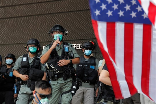 Riot police in front of an American flag near the U.S. Consulate in Hong Kong.