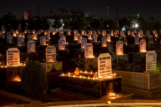 Candles on the graves of people killed during the Syrian war, Qamishli, Syria