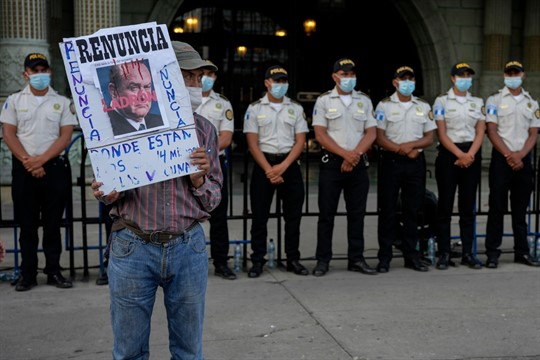 A protester holds a sign outside the National Palace in Guatemala City.