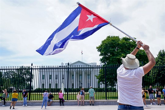 A man waves a Cuban flag at a rally outside the White House.