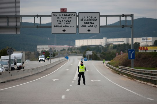 A police officer stands on a closed-off road near Igualada, Spain.