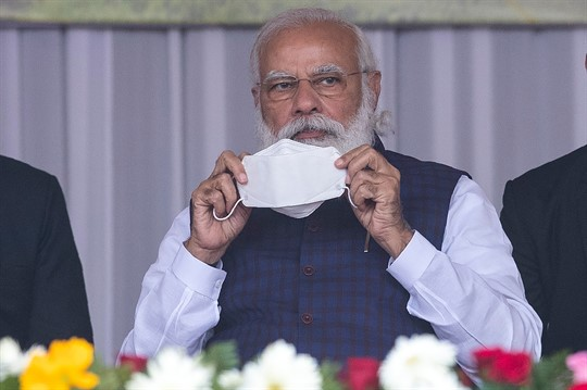 Indian Prime Minister Narendra Modi holds a face mask at a rally in Assam state.