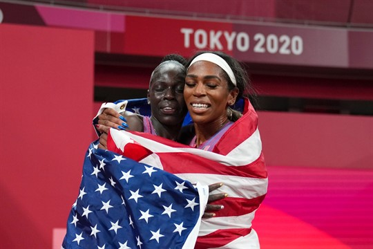 Two U.S. women athletes embrace, wrapped in a U.S. flag, at the Tokyo Olympics.