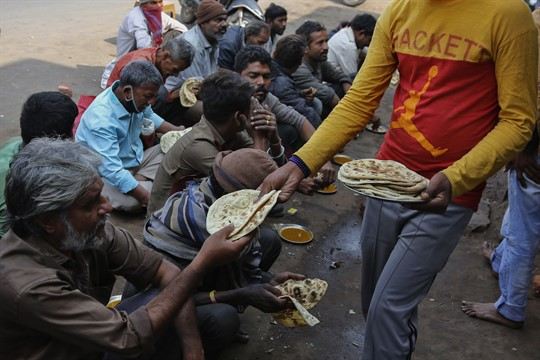 A man distributes free food outside an eatery in Ahmedabad, India