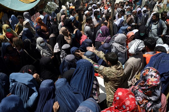 Internally displaced Afghans from northern provinces wait to receive free food in a public park