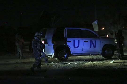Afghan security personnel in front of a United Nations vehicle in Kabul at night.