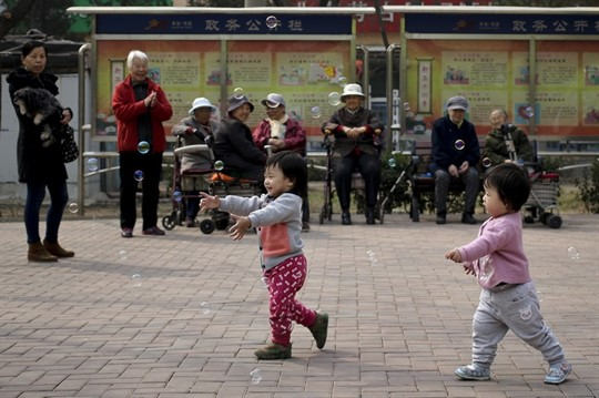 Older residents watching children play with bubbles at a residential compound in Beijing.