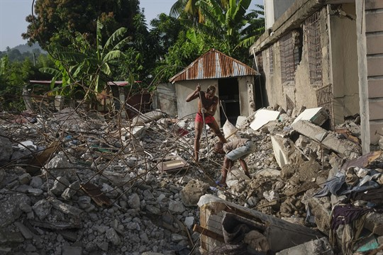 A man searches for his passport among the wreckage of his grandmother's house in Maniche, Haiti