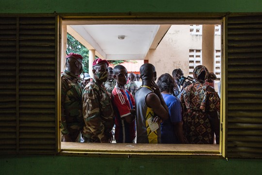 Civilians and soldiers line up to vote at a school in Conakry, Guinea in October 2020.
