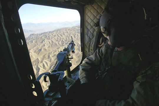 A U.S. Army doorgunner aboard a Chinook helicopter looks down onto the Afghan landscape.