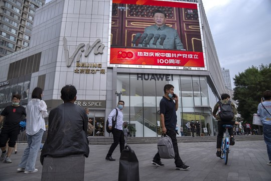People walk past a large video screen showing Chinese President Xi Jinping