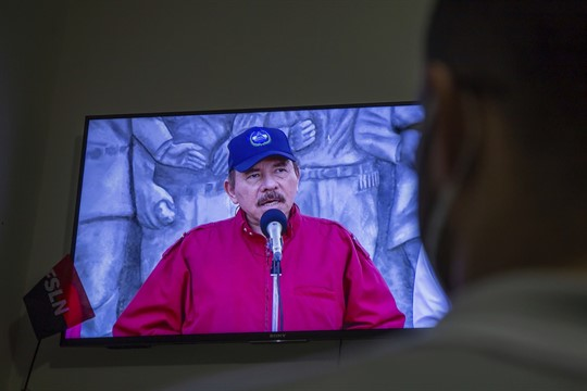 A man watches a televised national address by Nicaraguan President Daniel Ortega
