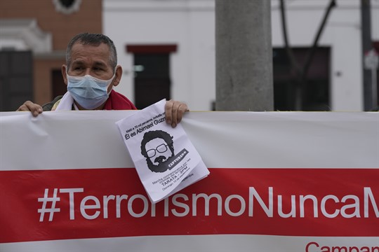 A man holds up a banner with a hashtag that reads in Spanish,