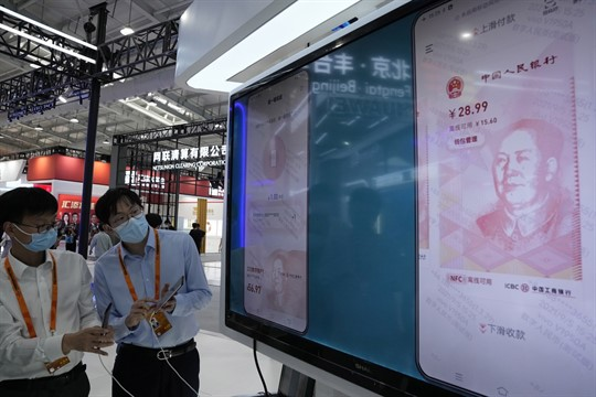 Workers demonstrate the use of the e-CNY, a digital version of the Chinese yuan.