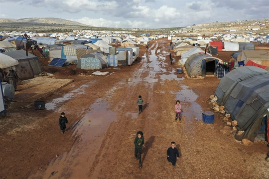An overhead view of Syrian children walking through a camp for displaced people in Idlib province