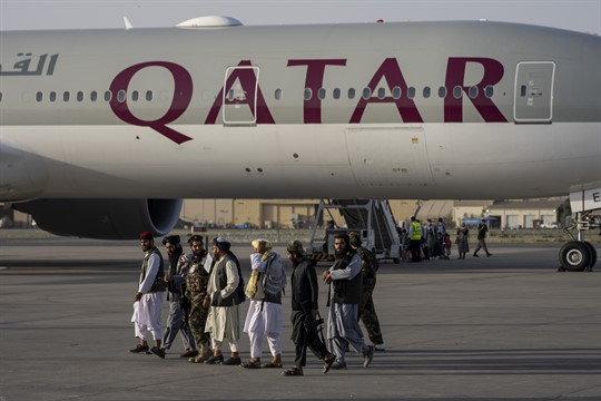Taliban fighters walk past a Qatar Airways aircraft at the airport in Kabul, Afghanistan.